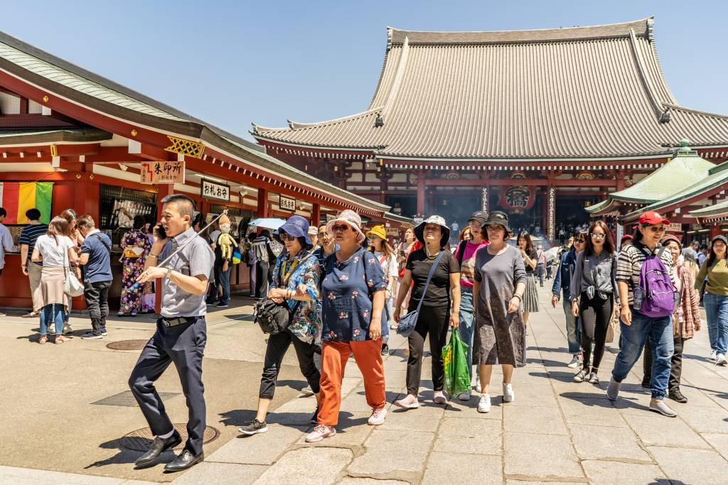 A group of tourists visits the historic Senso-Ji Temple in Askusa.